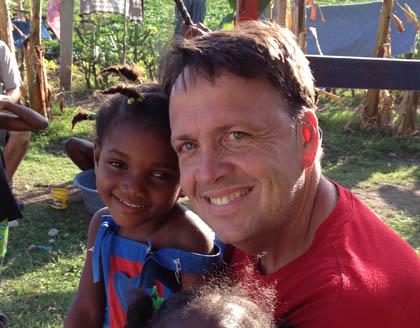 Conwell Larson holding Haitian girl